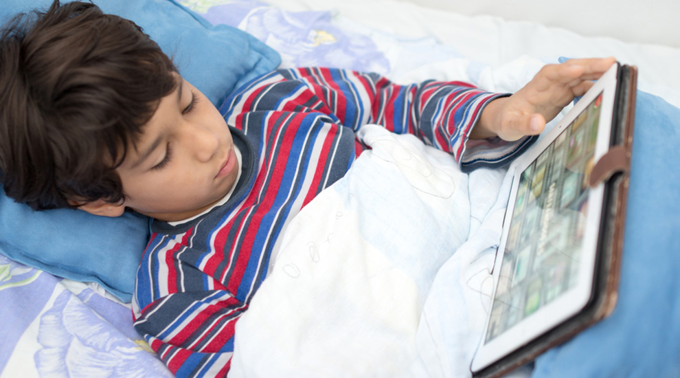 Ragazzino con fibrosi cistica consulta il tablet dal letto a casa propria