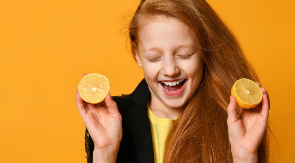 ragazza con fibrosi cistica sorride con due arance a metà